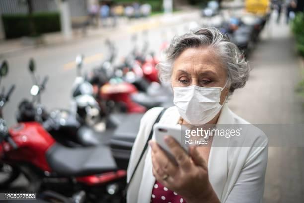 hogere onderneemster met masker het lopen gebruikend mobiel bij straat - mobile stockfoto's en -beelden