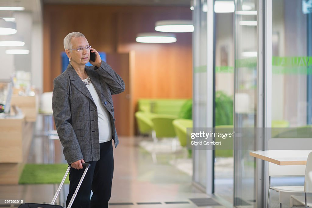 Senior businesswoman with wheeled suitcase chatting on smartphone in hotel lobby : Stock-Foto