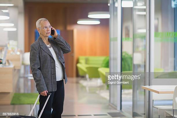 senior businesswoman with wheeled suitcase chatting on smartphone in hotel lobby - sigrid gombert stockfoto's en -beelden