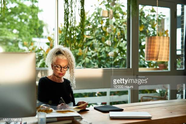 senior businesswoman working at home - working seniors stock pictures, royalty-free photos & images