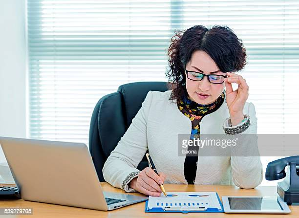 senior businesswoman writing in office