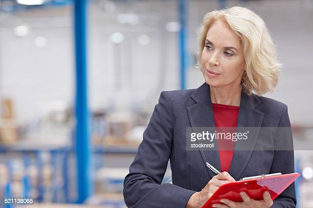 Senior businesswoman writing inventory