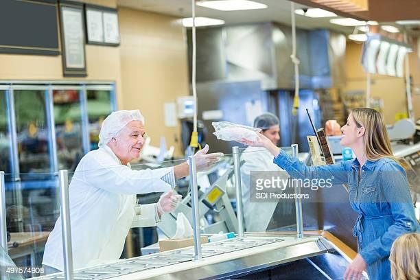 Senior Fleischer oder Mitarbeiter helfen Kunden im Supermarkt