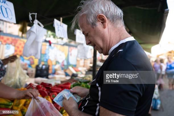 senior buying fruits on street market - bancarella di verdura foto e immagini stock