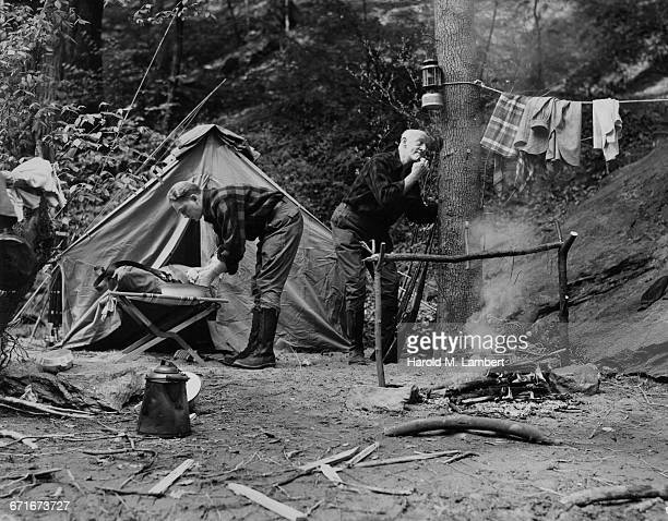 senior camper shaving and young camper washing his hands at camp site - {{ contactusnotification.cta }} stockfoto's en -beelden