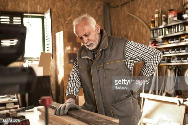 senior carpenter having back pain - personal injury stock photos and pictures