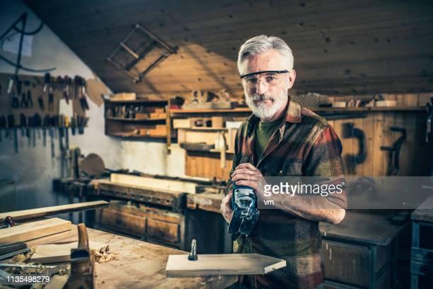 charpentier aîné retenant une scie électrique - bricolage photos et images de collection