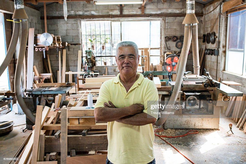 A senior carpenter in his workshop : Stock Photo