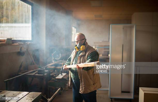senior carpenter posing in front of camera with safety mask - wind instrument stock pictures, royalty-free photos & images