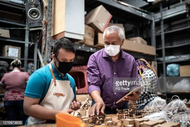 senior schreiner lehre junge mitarbeiter, beide tragen gesichtsmaske - persons with disabilities stock-fotos und bilder