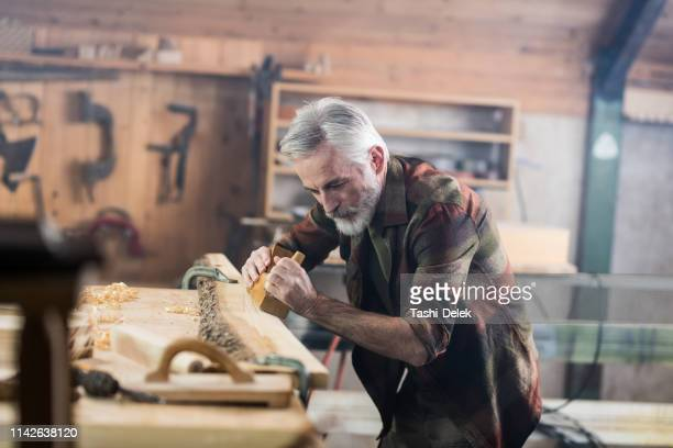 senior carpenter working in his old-fashion workshop - carpenter stock pictures, royalty-free photos & images