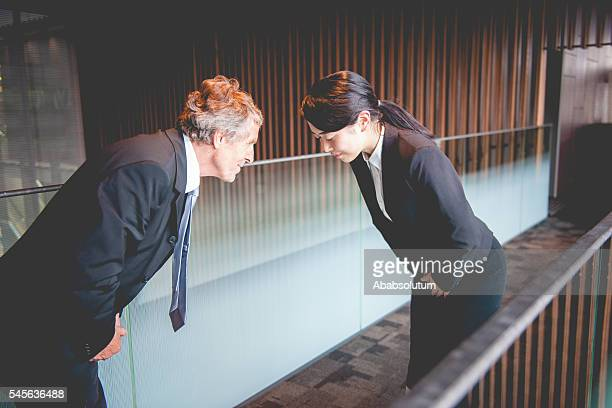 Senior Caucasian Businessman and Young Japanese Entrepreneur Bowing, Kyoto, Japan