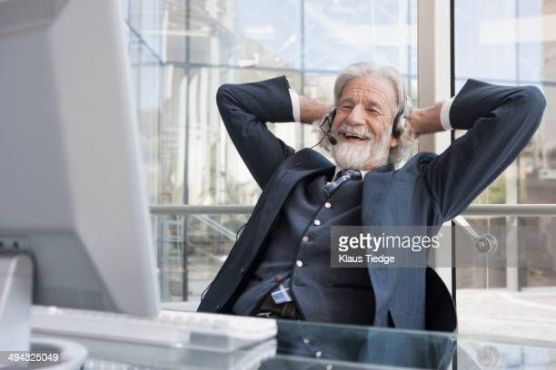 senior caucasian businessman talking on headset - bluetooth stock pictures, royalty-free photos & images