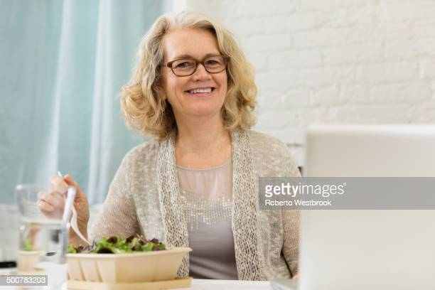 senior caucasian businesswoman eating salad - roberto ricciuti foto e immagini stock