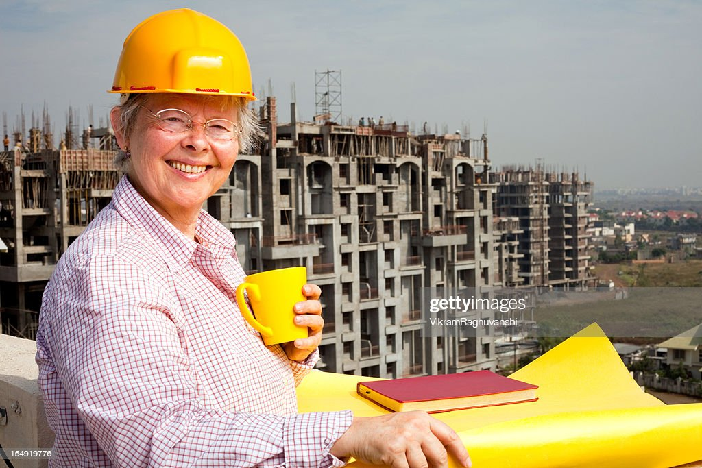 Senior caucasian cheerful woman engineer architect with blueprint senior caucasian cheerful woman engineer architect with blueprint holding coffee stock photo malvernweather Choice Image