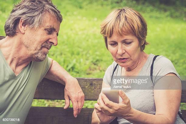 Senior europäischer Abstammung paar Überprüfung der Smartphone im Freien