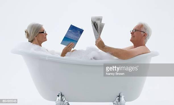 Senior Caucasian Couple in bubble bath reading