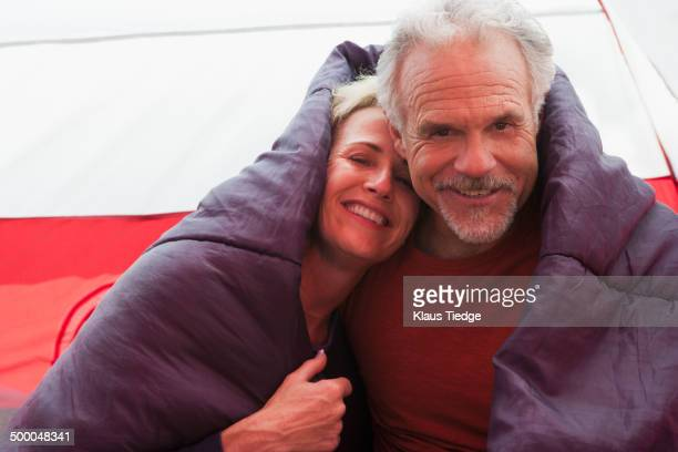 Senior Caucasian couple in sleeping bag in tent