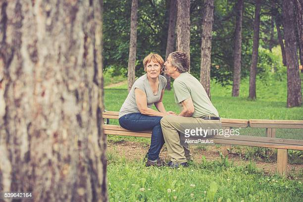 Senior caucasian couple kissing, whispering and holding hands outdoors