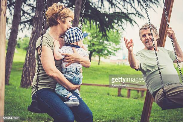 Senior caucasian couple outdoors with their grandson in city park