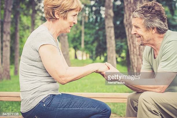 Senior caucasian couple smiling, talking and holding hands outdoors