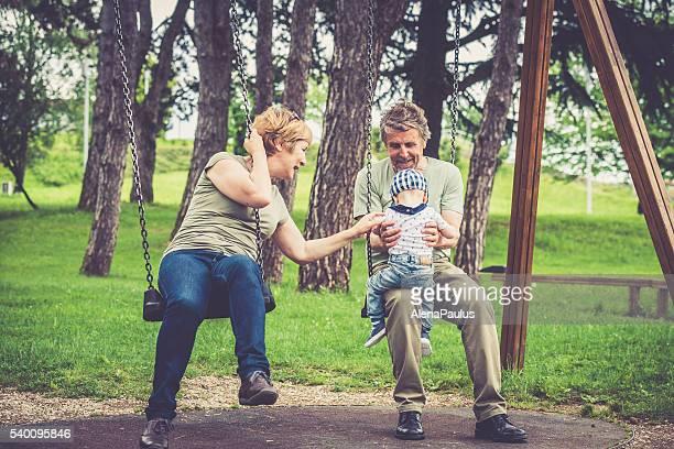 Senior caucasian couple swinging with their grandson in city park