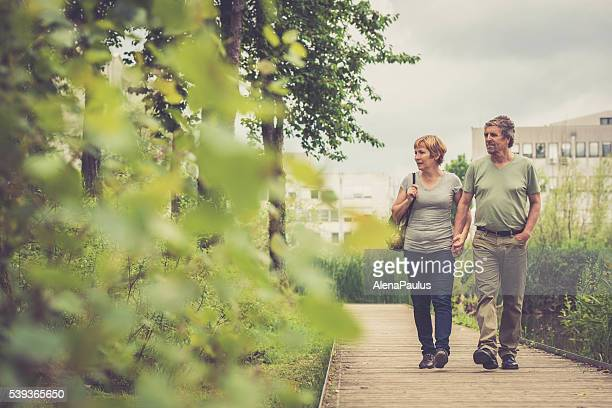Senior caucasian couple walking, holding hands and looking outdoors