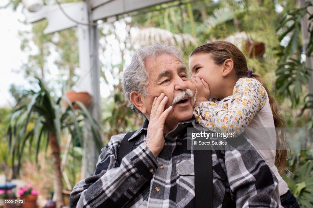 Senior Caucasian man and granddaughter whispering outdoors : Stock Photo