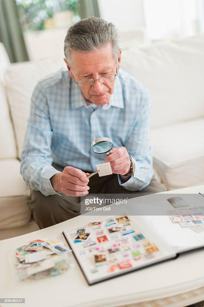 Senior Caucasian man examining stamp collection : Stock Photo