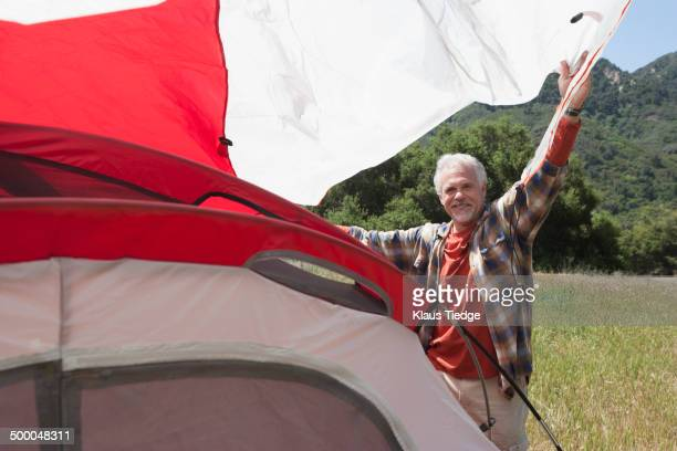 senior caucasian man pitching tent in field - only mature men stock pictures, royalty-free photos & images