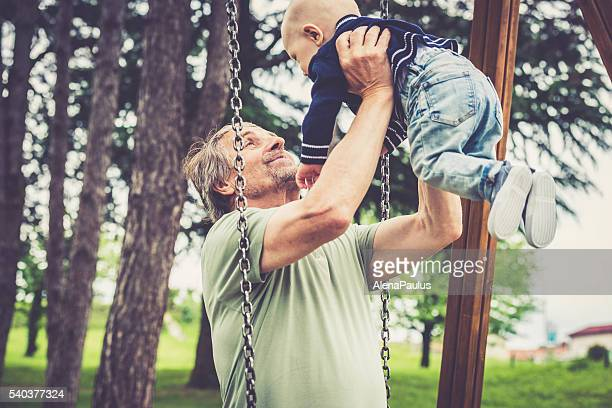 Senior caucasian man playing with his grandson in city park