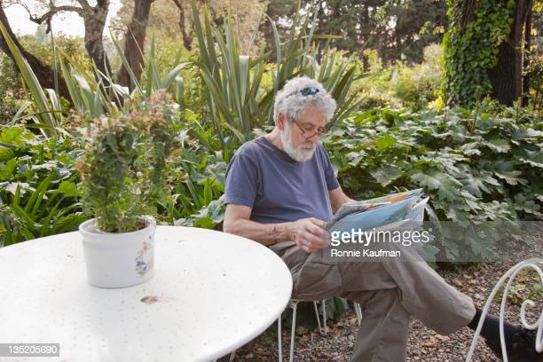 senior caucasian man reading newspaper outdoors - one man only stock pictures, royalty-free photos & images