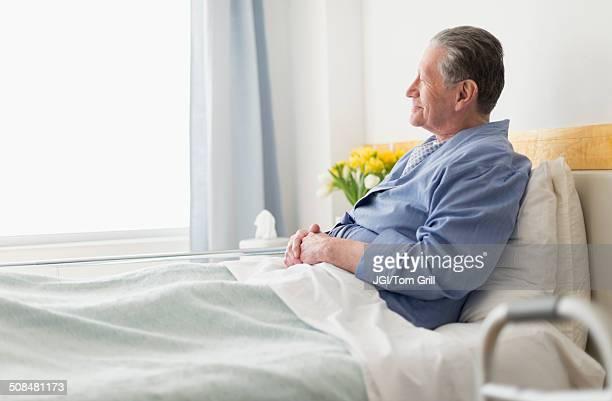 Senior Caucasian man sitting in hospital bed