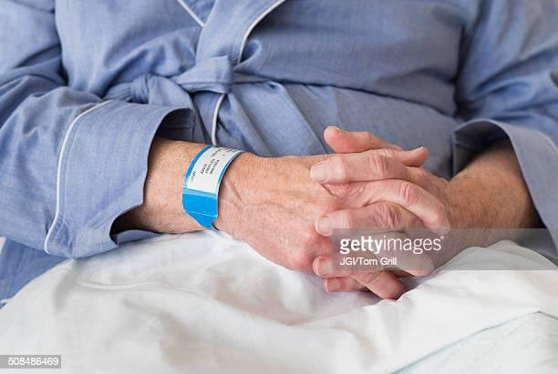 senior caucasian man sitting in hospital bed - pulsera fotografías e imágenes de stock