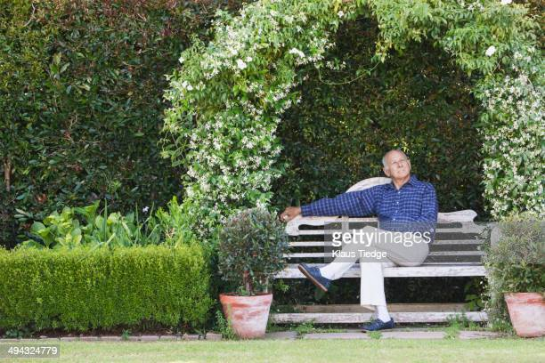 Senior Caucasian man sitting on garden bench