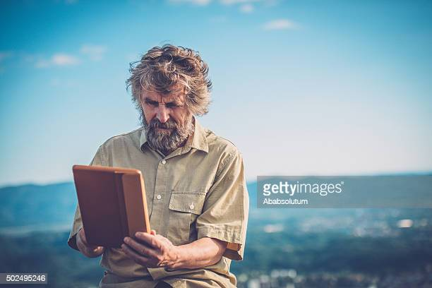 Senior Caucasian Man Taking Selfie with Tablet at Old Ruins