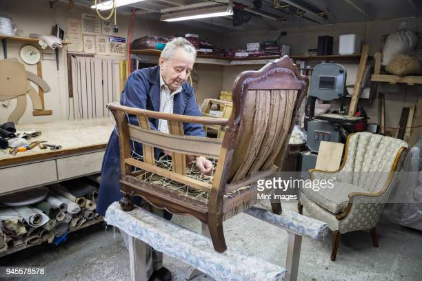 Senior Caucasian man upholsterer working on an antique chair in his garage shop.