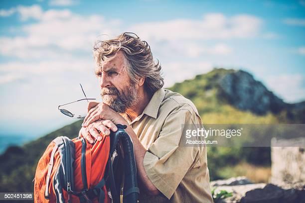 Senior europäischer Abstammung Mann mit Orange Rucksack im alten Ruinen