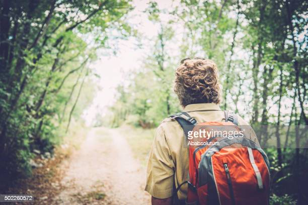Senior Caucasian Man with Sunglasses and Beard Hiking in Forest