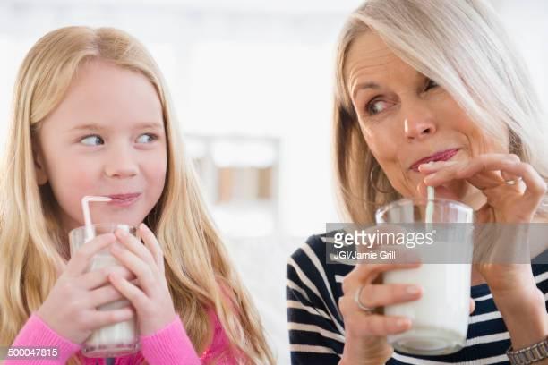 Senior Caucasian woman and granddaughter drinking milk