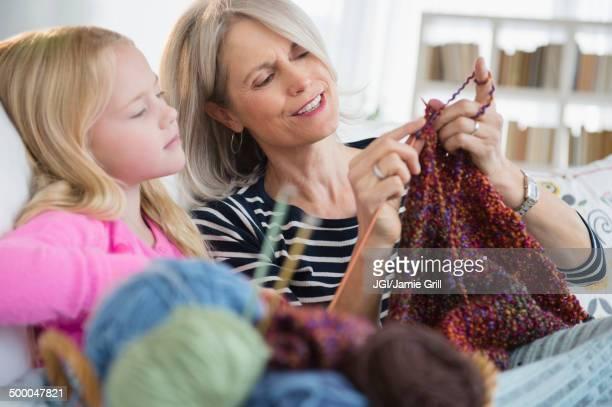 Senior Caucasian woman and granddaughter knitting on sofa