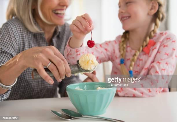Senior Caucasian woman and granddaughter making ice cream sundae
