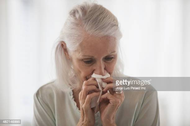 Senior Caucasian woman blowing her nose