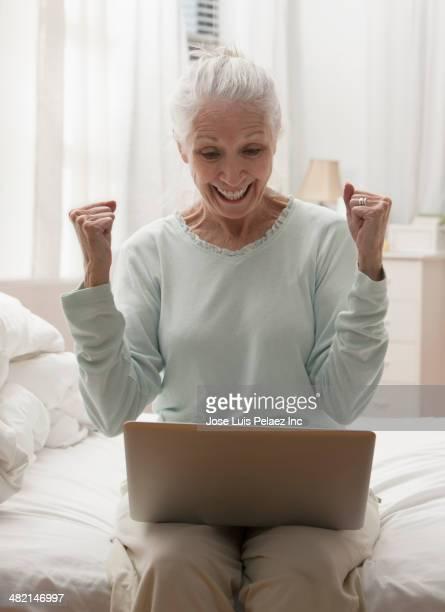 Senior Caucasian woman cheering at laptop in bedroom
