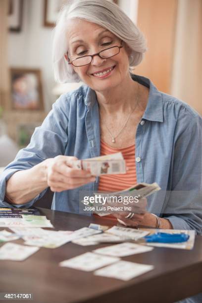 senior caucasian woman clipping coupons - coupon stock photos and pictures