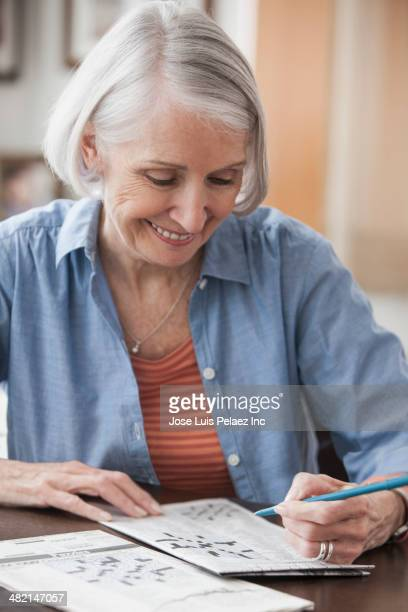 Senior Caucasian woman doing crossword puzzle