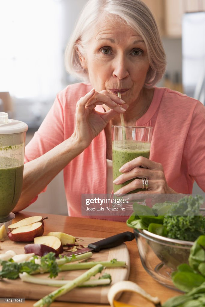 Senior Caucasian woman drinking green smoothie : Stock-Foto