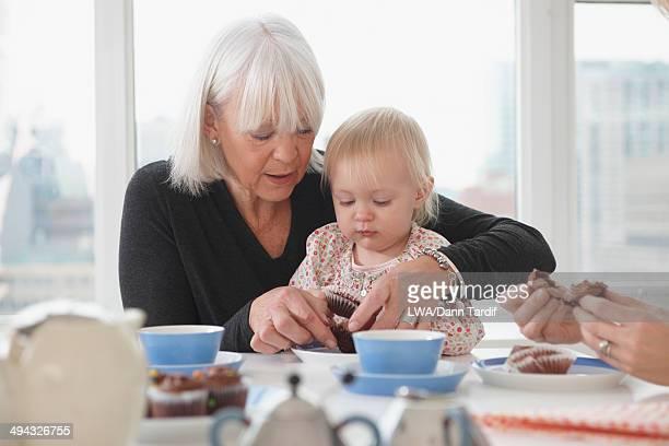 Senior Caucasian woman feeding granddaughter cupcakes