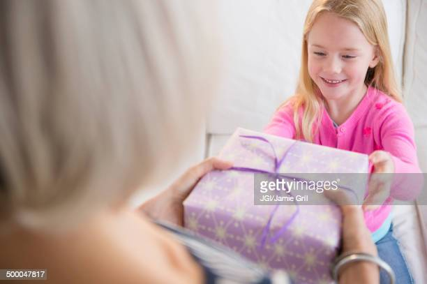 senior caucasian woman giving granddaughter present - receiving stock pictures, royalty-free photos & images
