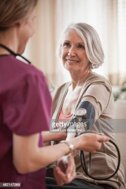 Senior Caucasian woman having blood pressure checked by nurse